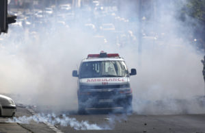 A Palestinian ambulance emerges from a cloud of tear gas.