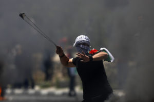 "A Palestinian protester hurls a stone during clashes with Israeli forces after a rally to mark the 70th anniversary of what Palestinians call their ""nakba."""