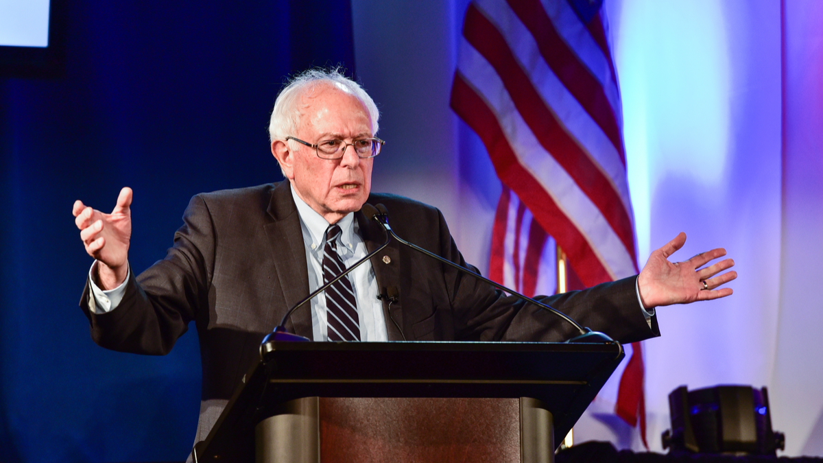 Picture of Sen. Bernie Sanders speaking with American flag in the background
