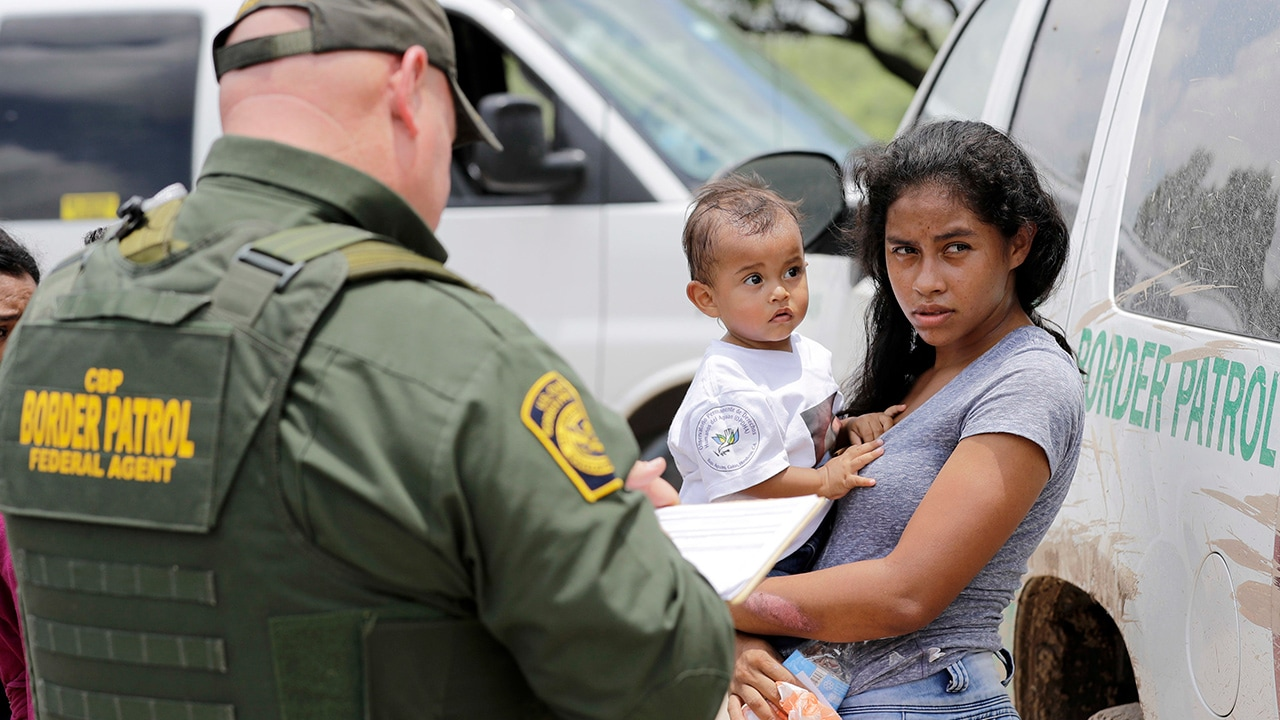 Photo of a mother and her child surrendering to U.S. Border Patrol agents
