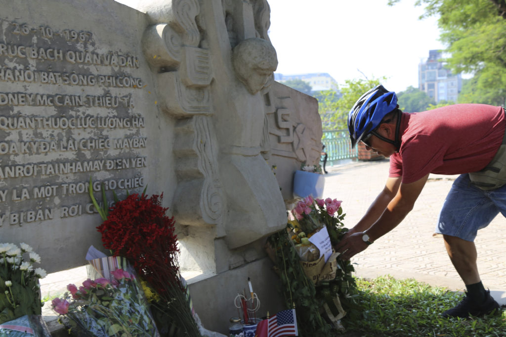 Photo of Vietnamese man laying flowers at the memorial for John McCain in Hanoi