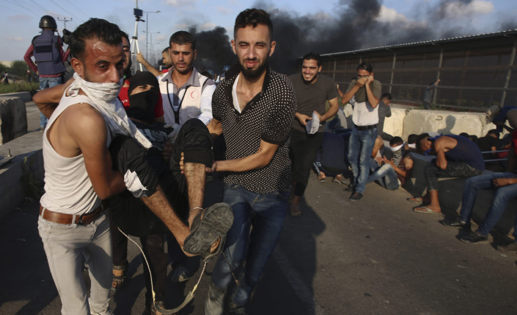 Photo of medic evacuating wounded youth during protest in Gaza