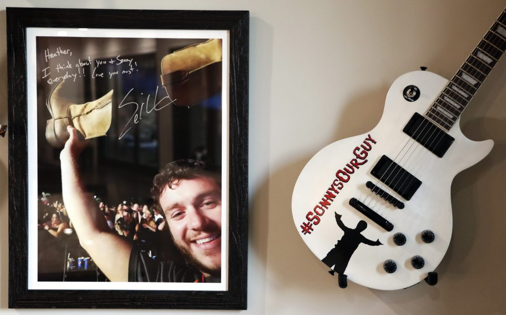 Photo of a picture of Sonny Melton, autographed by Eric Church, and a guitar from the Eric Church fan club