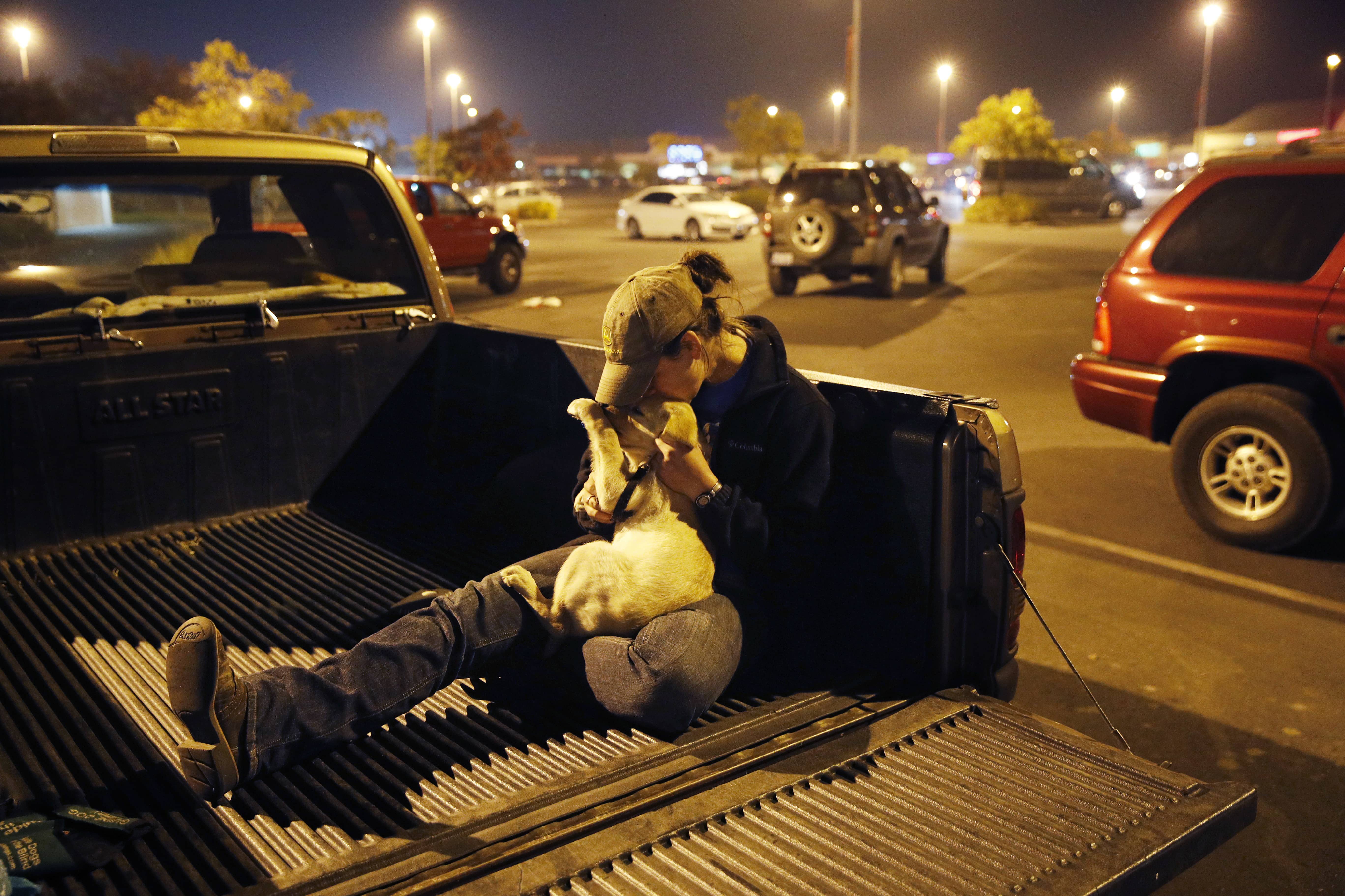 Photo of a California wildfire victim kissing her dog in the bed of her truck