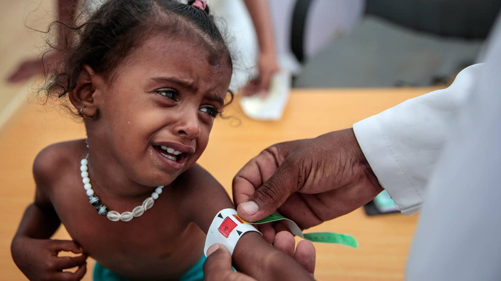 Photo of a Yemeni child getting her arm measured