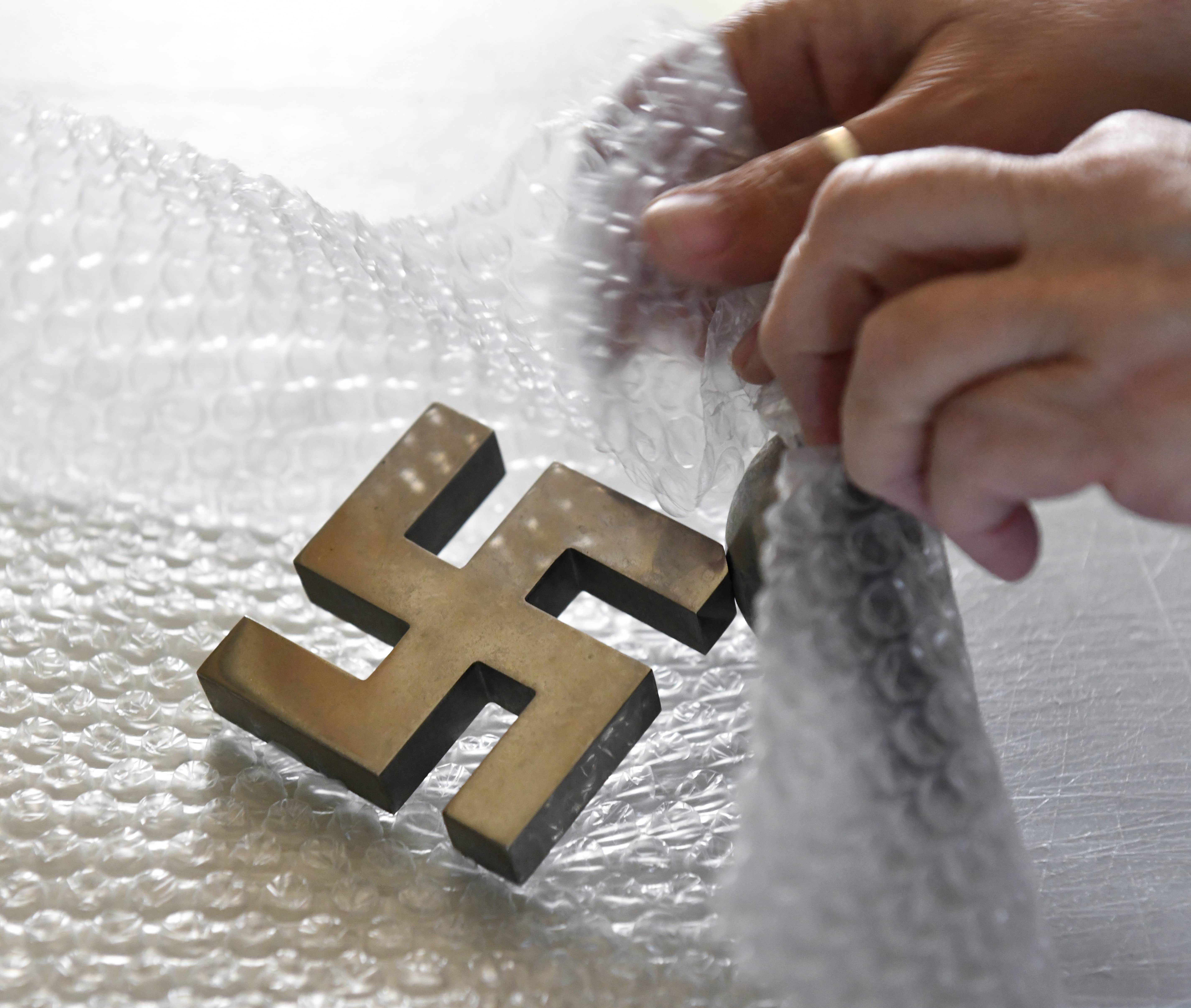 Photo of Tammy Pearce packing a recently sold swastika desk ornament