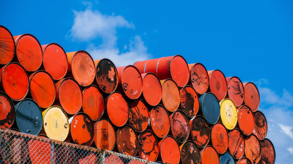 photo of stacked up empty oil barrels