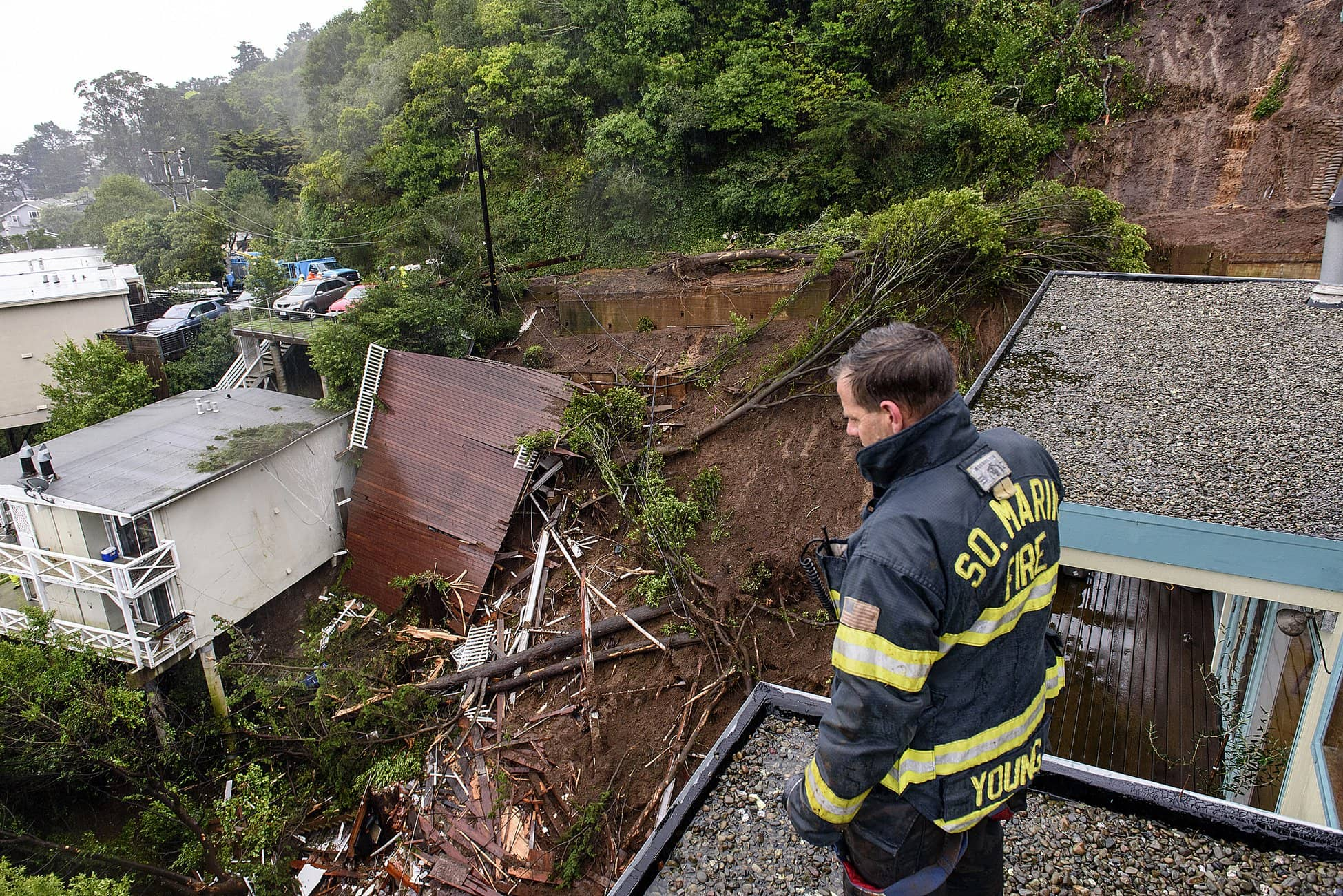 Photo of firefighter looking at wreckage caused by mudslide in California
