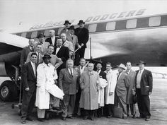 Photo of officials and employees of the Brooklyn Dodgers posed in front of the club's plane in New York City before leaving for Los Angeles