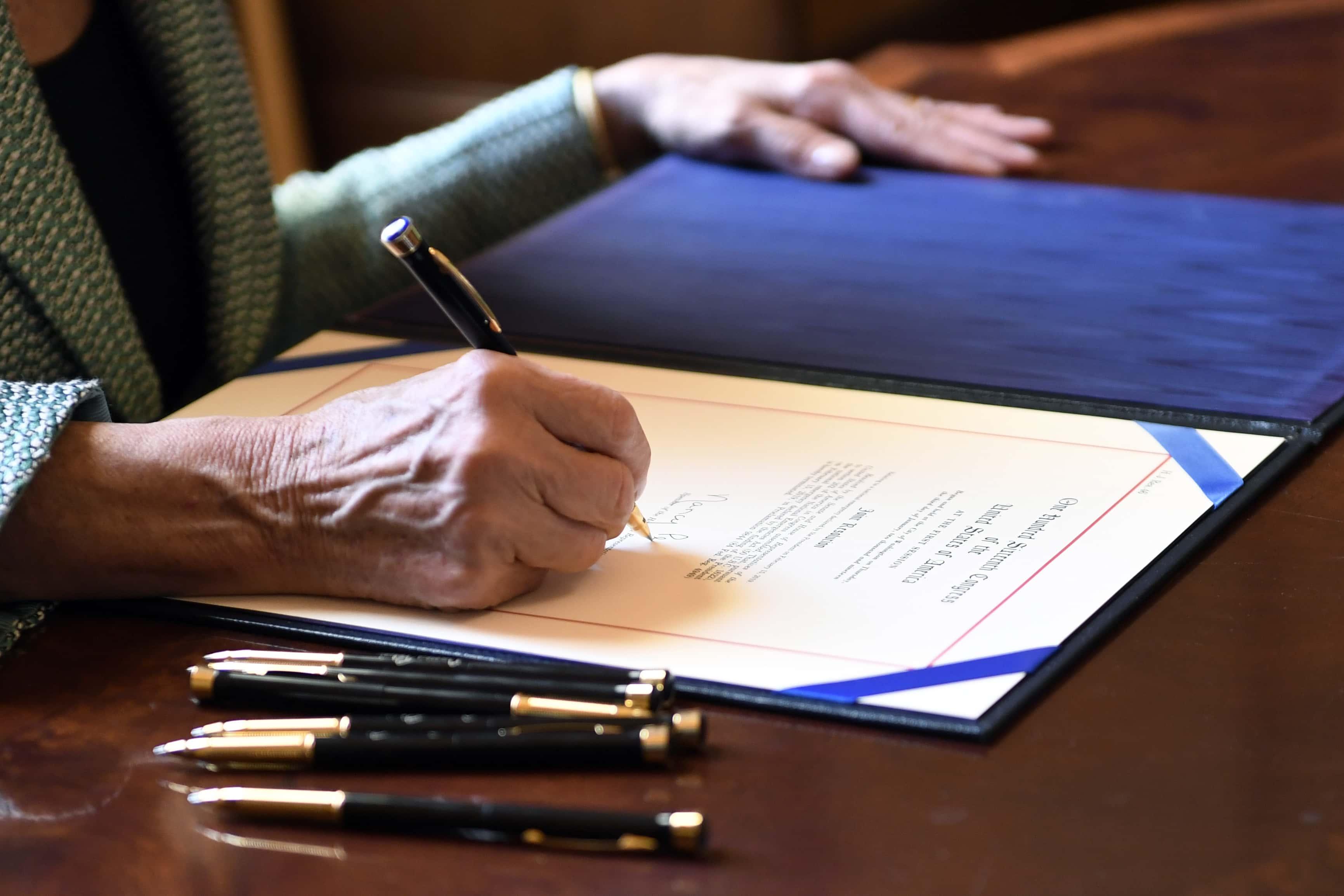 Photo of Nancy Pelosi signing H.J. Res 46