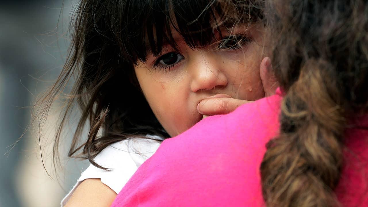 Photo of Hillary Herrera Cortez peering over her mother's shoulder