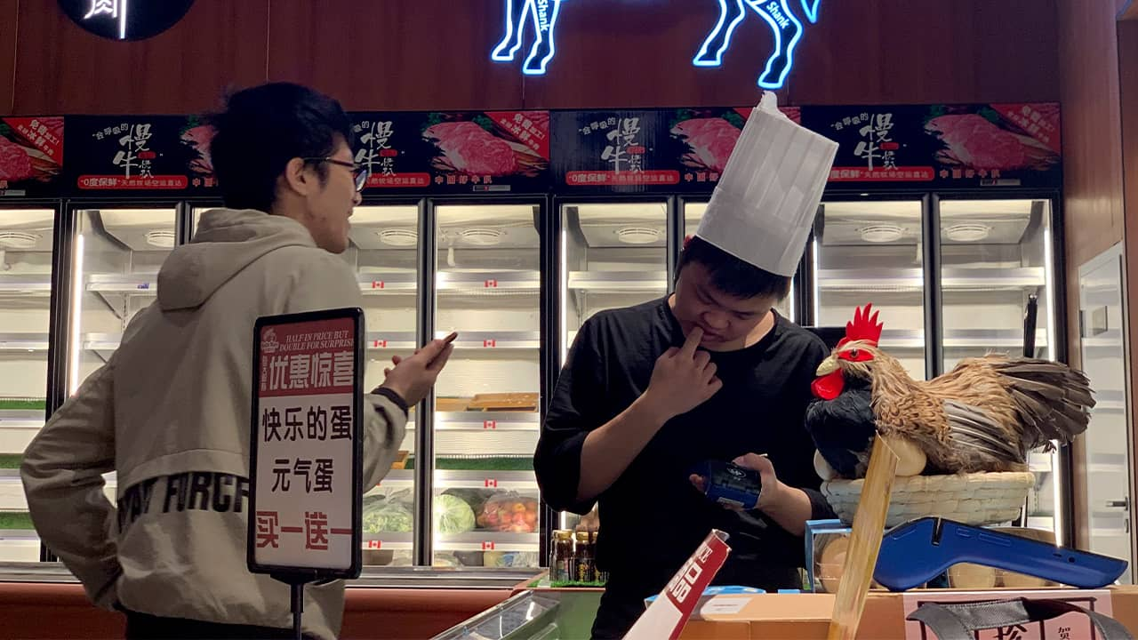 Photo of worker at the imported beef section of a supermarket
