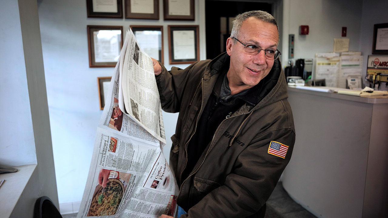 Photo of Phil Viscuso flipping through a copy of The Berkshire Eagle Newspaper