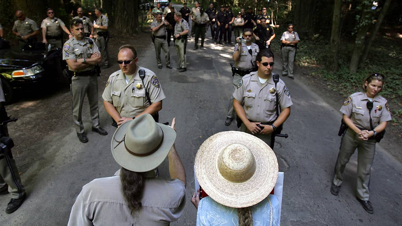Photo of protestors trying to talk with CHP officers as they block off the entrance to the Bohemian Grove retreat