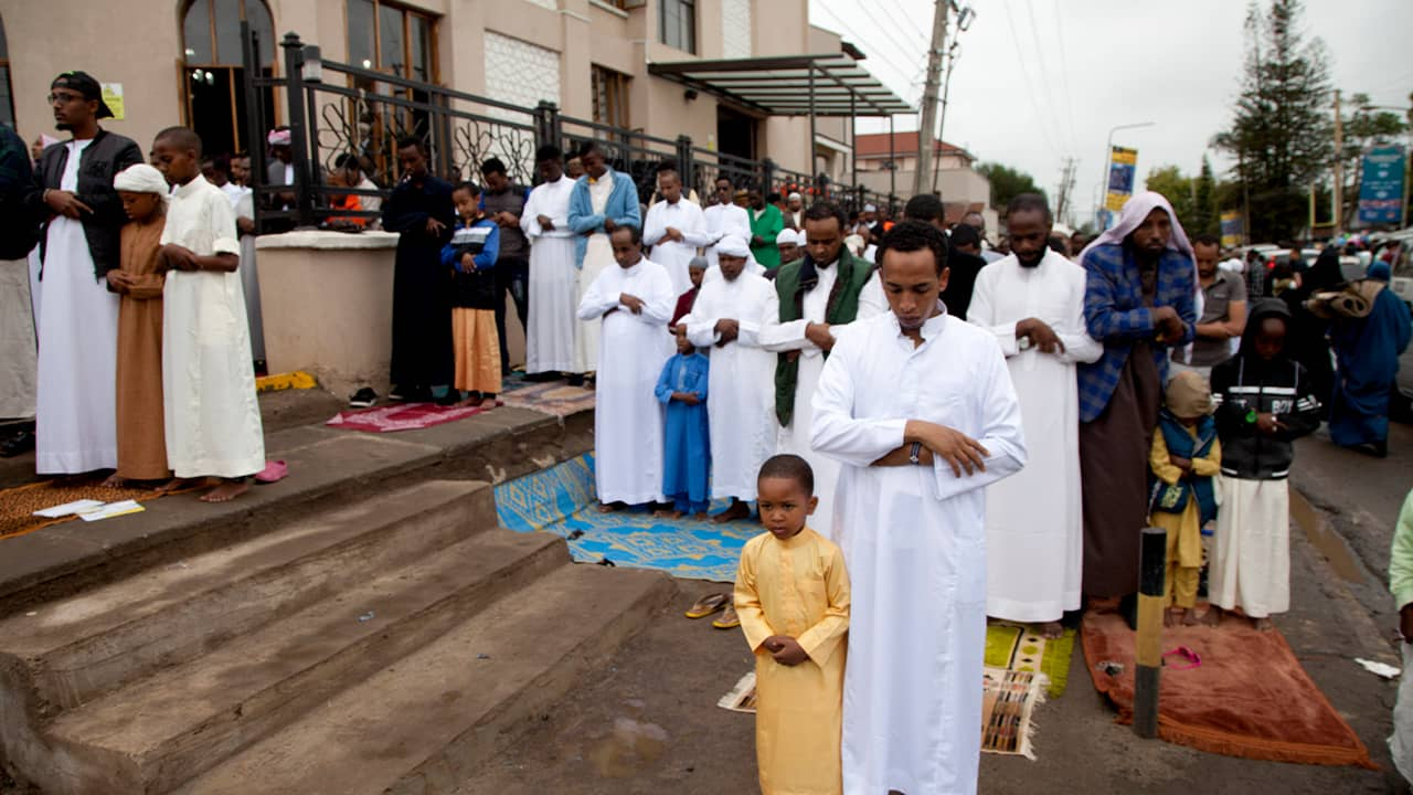 Photo of Kenyan Muslims standing for prayers outside Masjid As Salaam