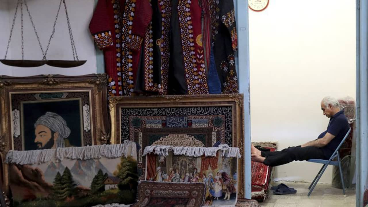 Photo of a carpet seller sitting at his shop in the main bazaar