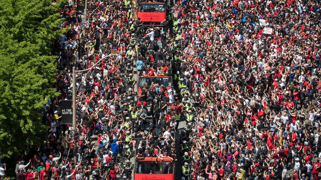 Photo of members of the Toronto Raptors riding on buses during a victory parade in Toronto