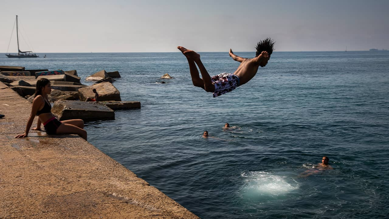 Photo of a boy jumping into the water in Spain