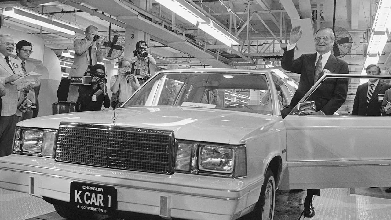 Photo of Lee Iacocca waving as he steps into the first K-Car in 1980