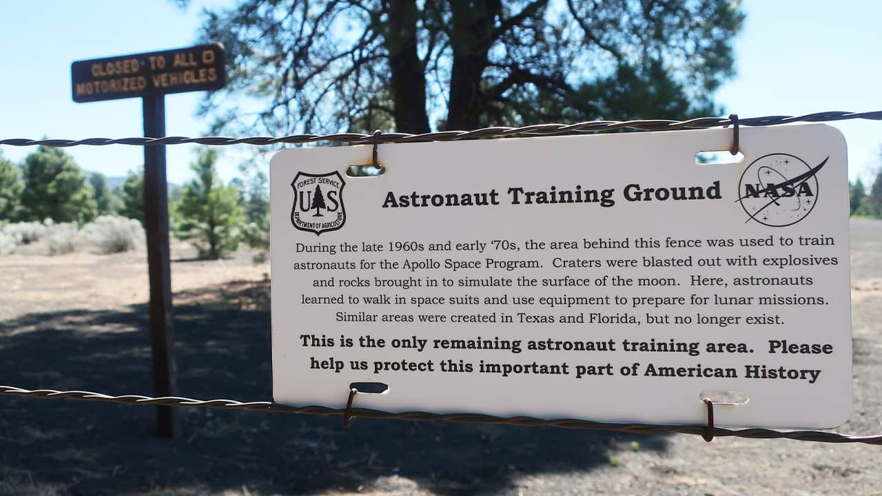 Photo of a sign and fenced off field of craters in a volcanic cinder field