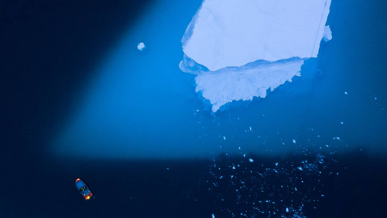 Photo of a boat navigating next to a large iceberg