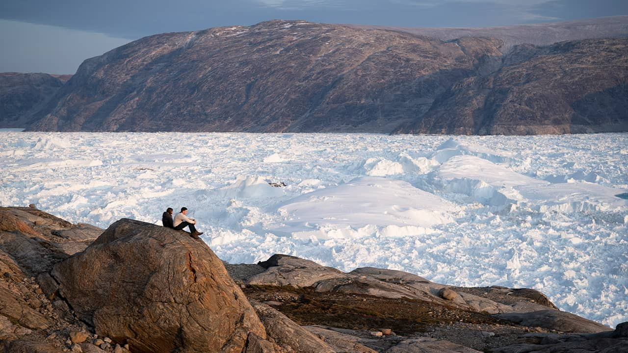 Photo of researchers sitting on a rock overlooking the Helheim glacier in Greenland