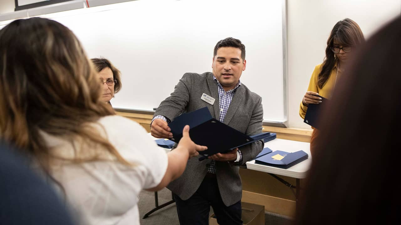 Photo of Jorge Arroyo handing out certificates