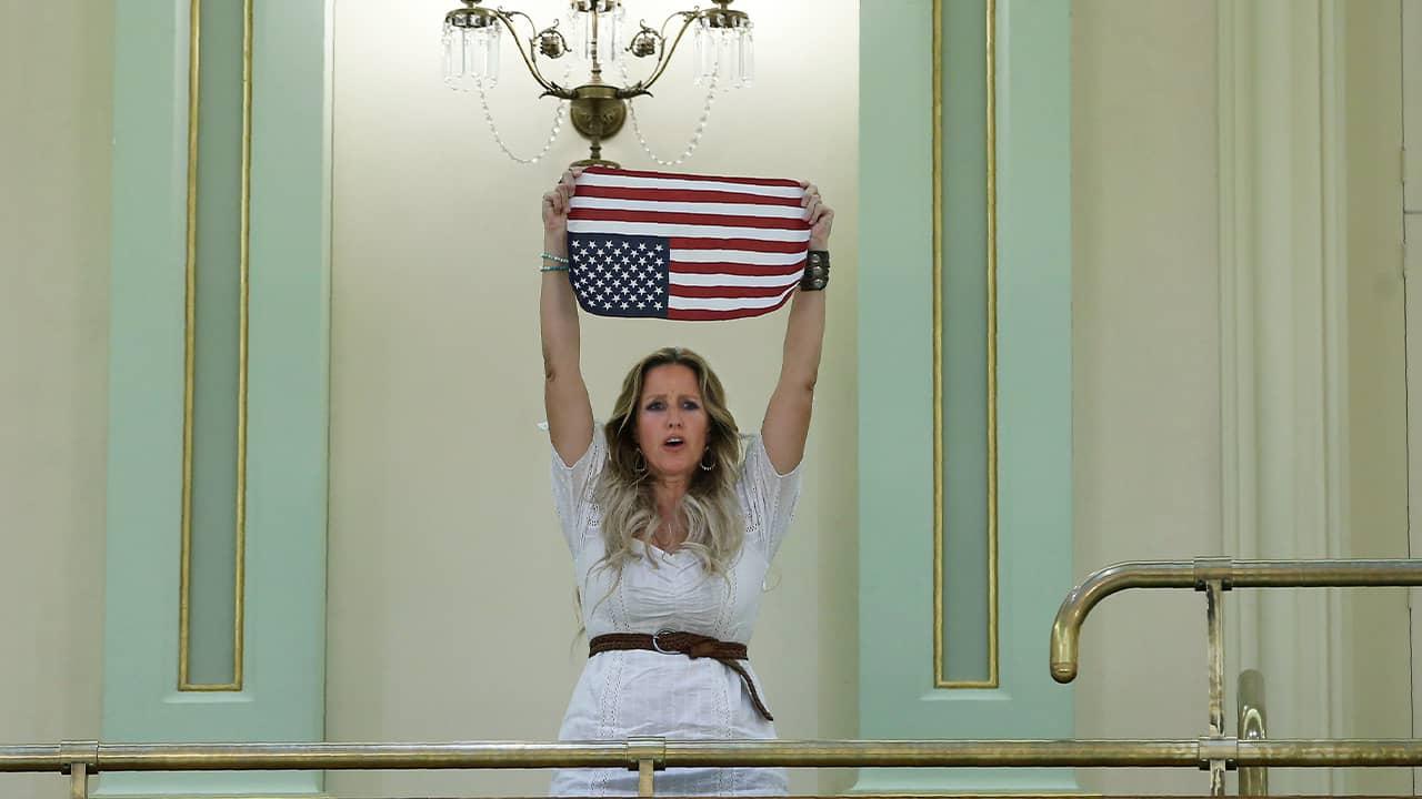 Photo of Tara Thornton holding an American flag upside down