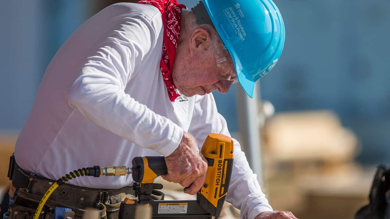 Photo of former President Jimmy Carter working with volunteers on site