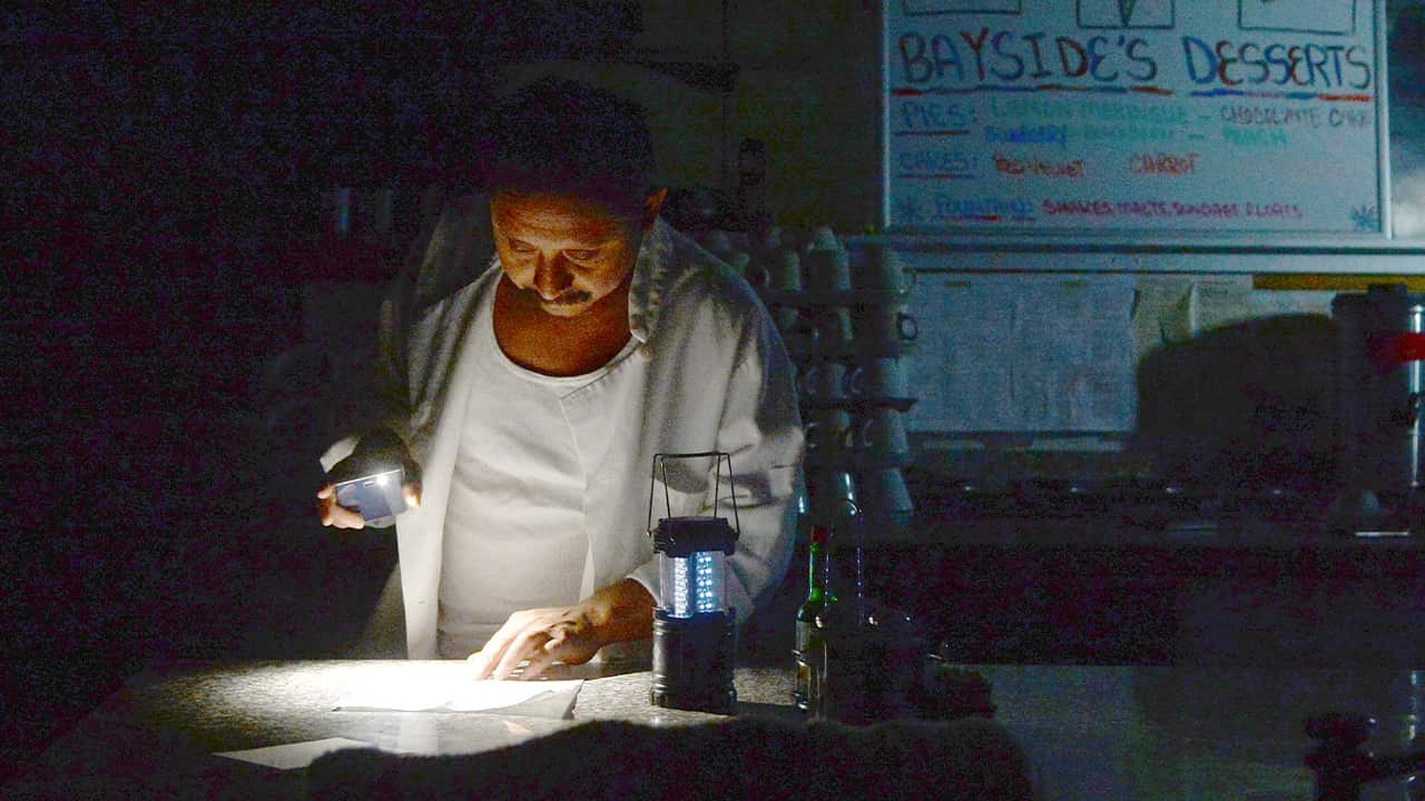 Photo of Carlos Lama using an LED lamp and his phone in his restaurant