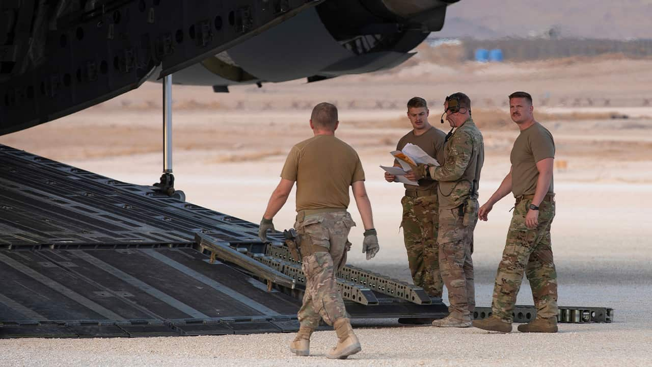 Photo of U.S. Airmen checking their manifest