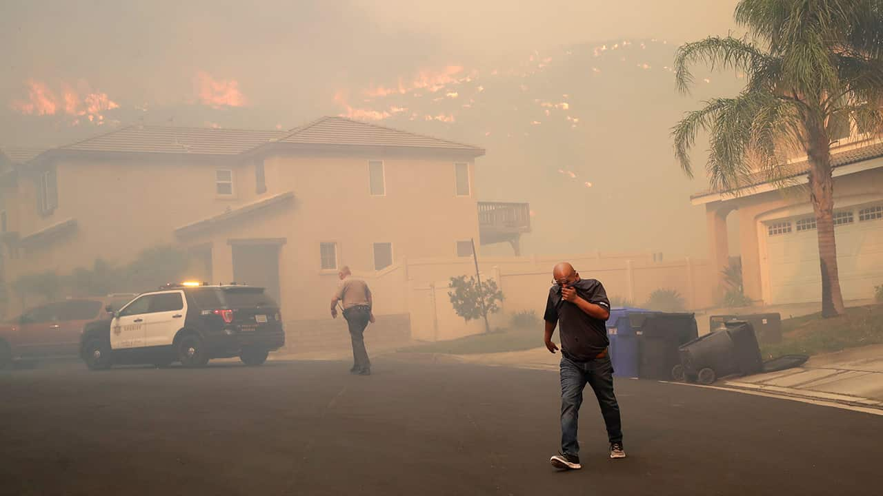 Photo of a resident covering his face as he is evacuated