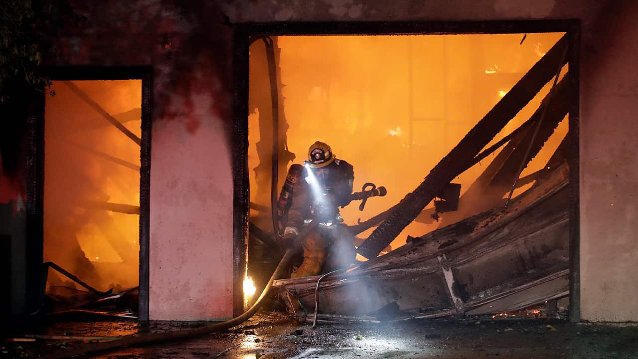 Photo of firefighter in a ravaged home