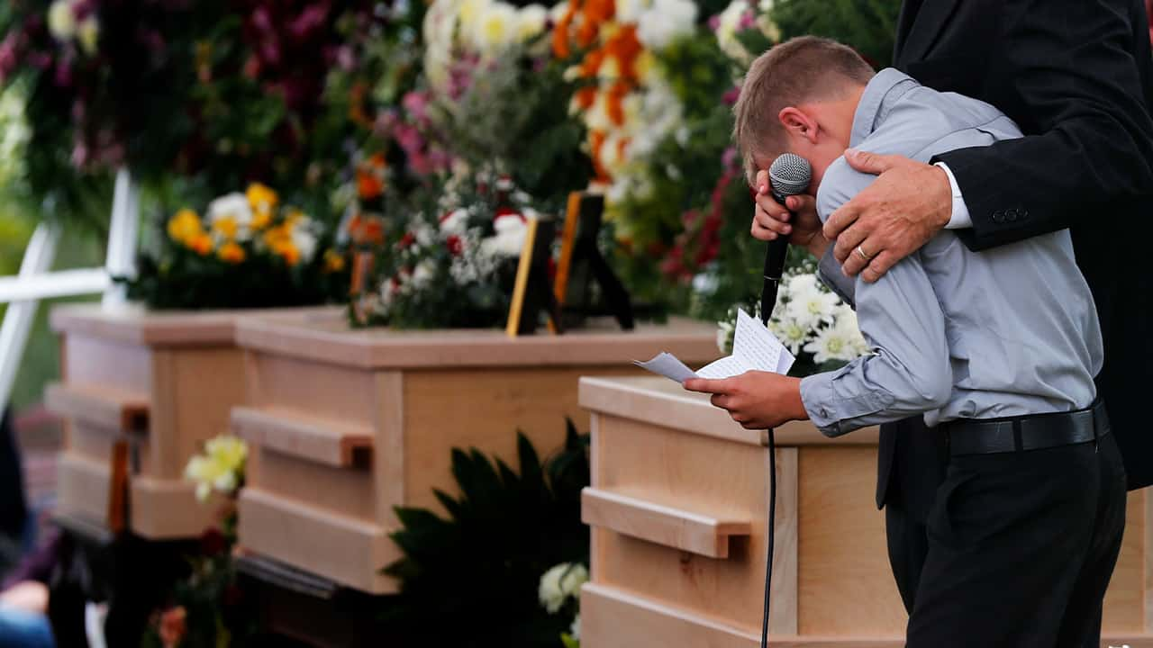 A boy pauses as he speaks at a funeral