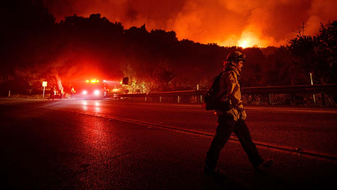 Photo of a firefighter crossing Highway 154 while battling the Cave Fire