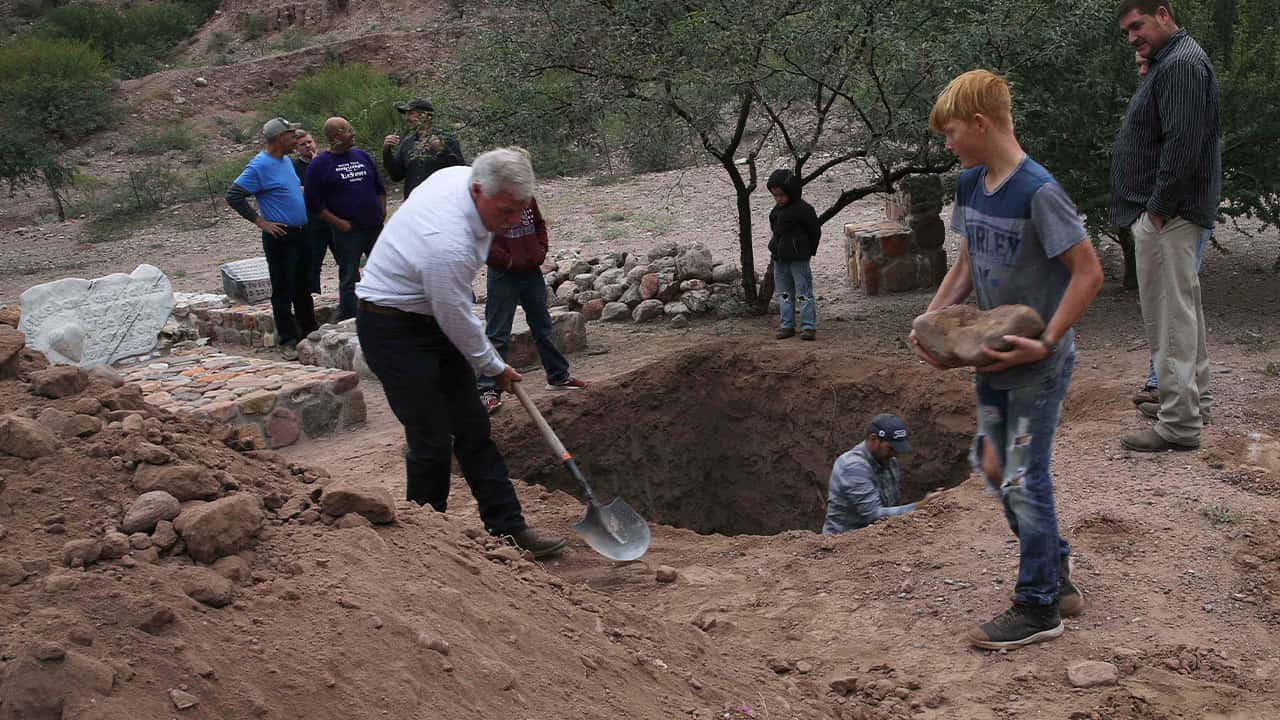 Photo of men digging a grave