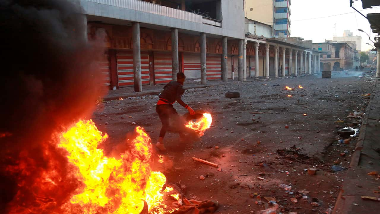 Photo of riot police firing tear gas while protesters set a fire