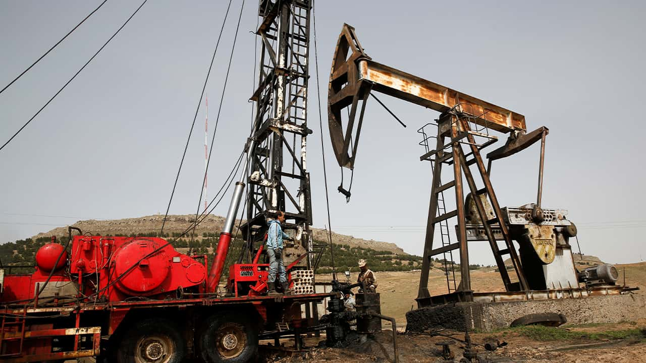 Photo of Syrian workers fixing pipes of an oil well