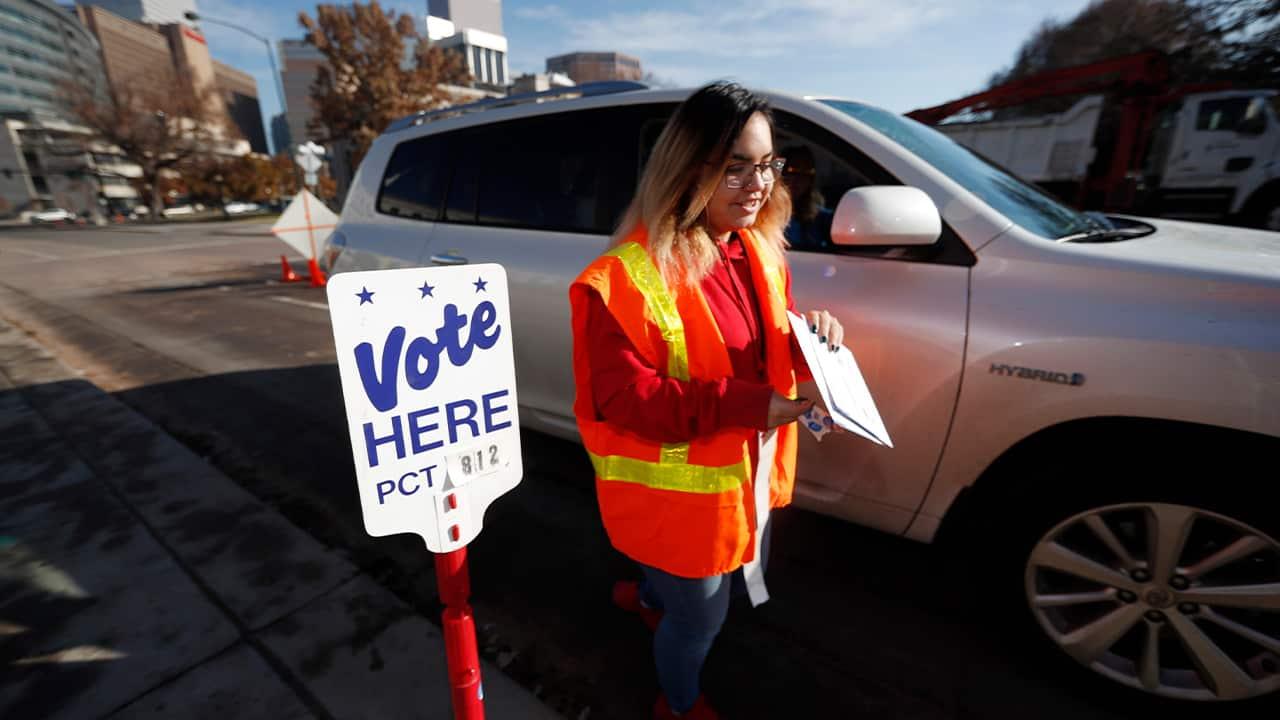 Photo of an election judge collecting a ballot