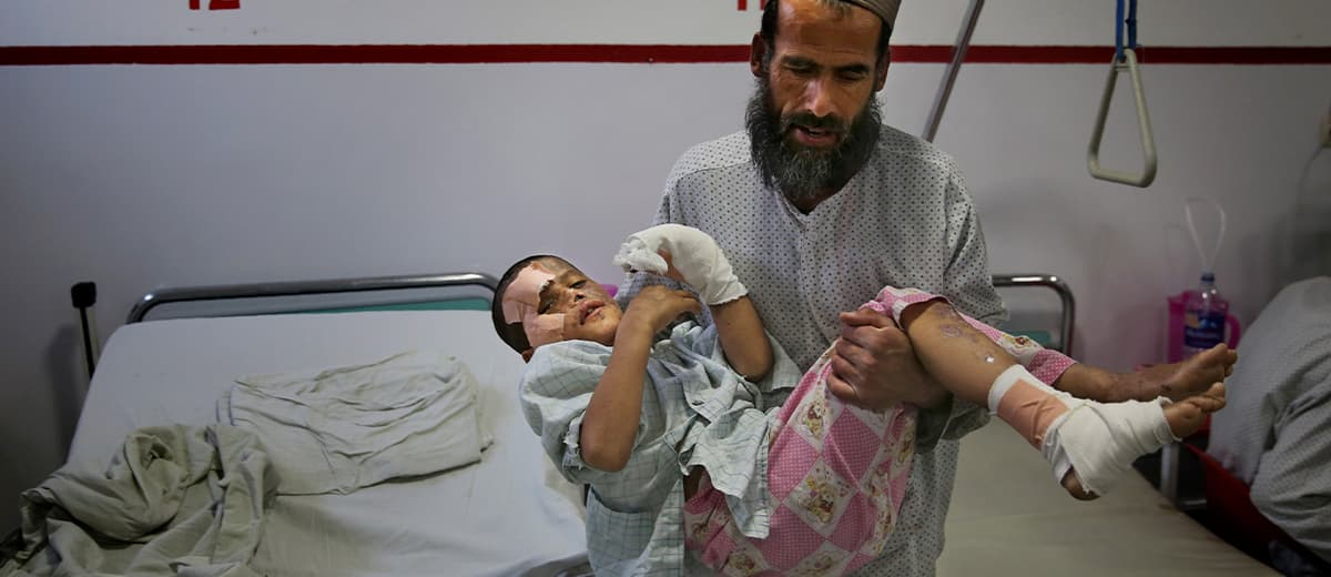 Photo of Ismatullah carrying his 9-year-old son