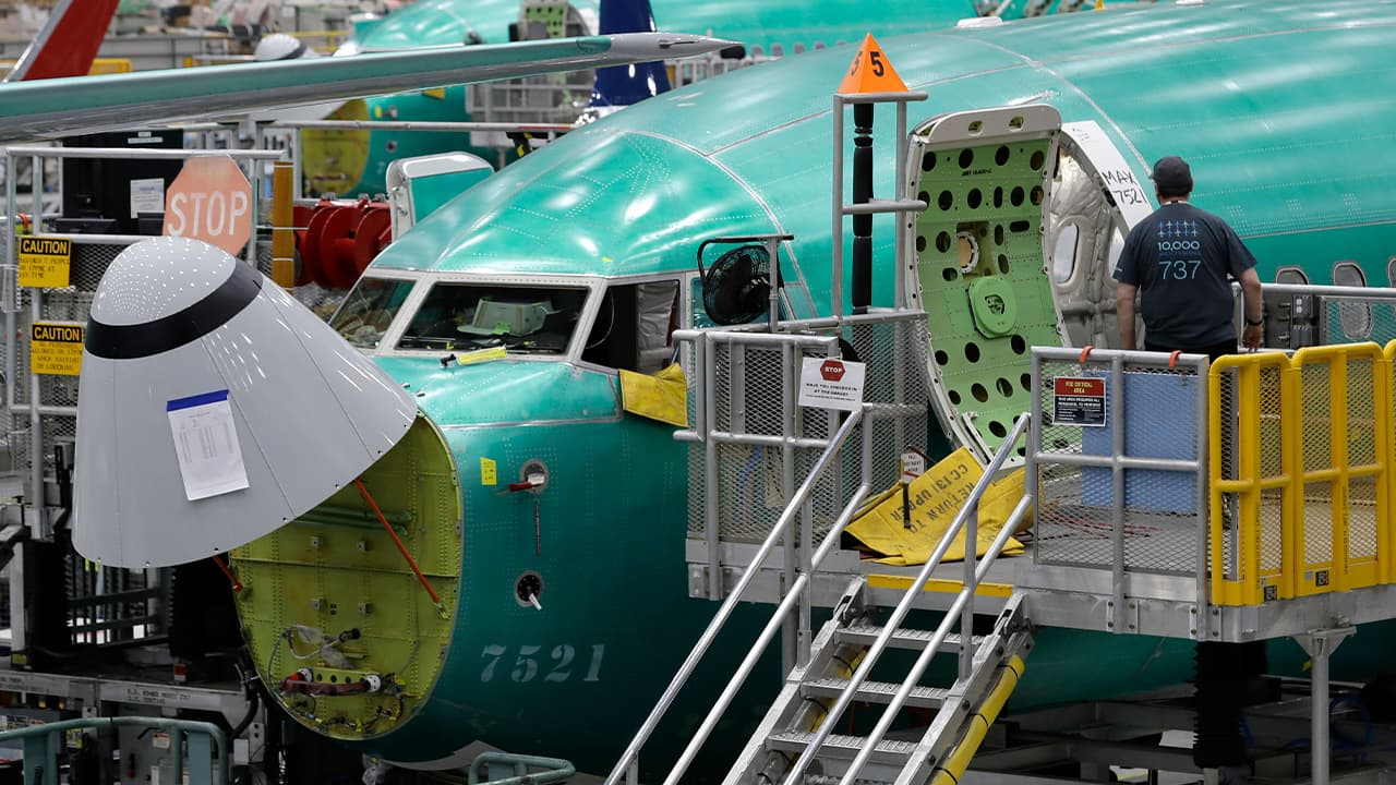 Photo of a working entering a Boeing 737 MAX 8 airplane