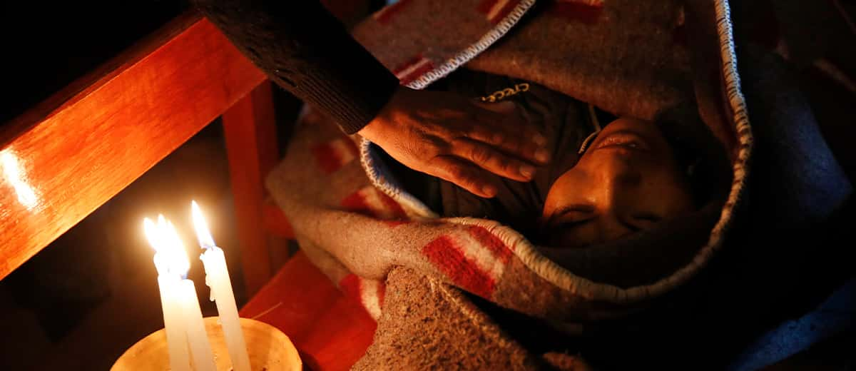 Photo of a mourner placing his hand on the shoulder of Devi Posto