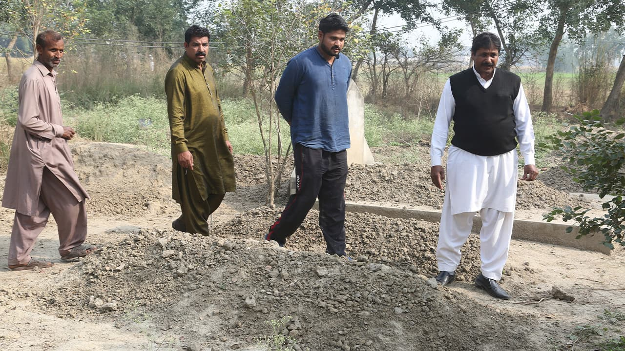 Photo of Samiya David's family visiting her unmarked grave in Pakistan