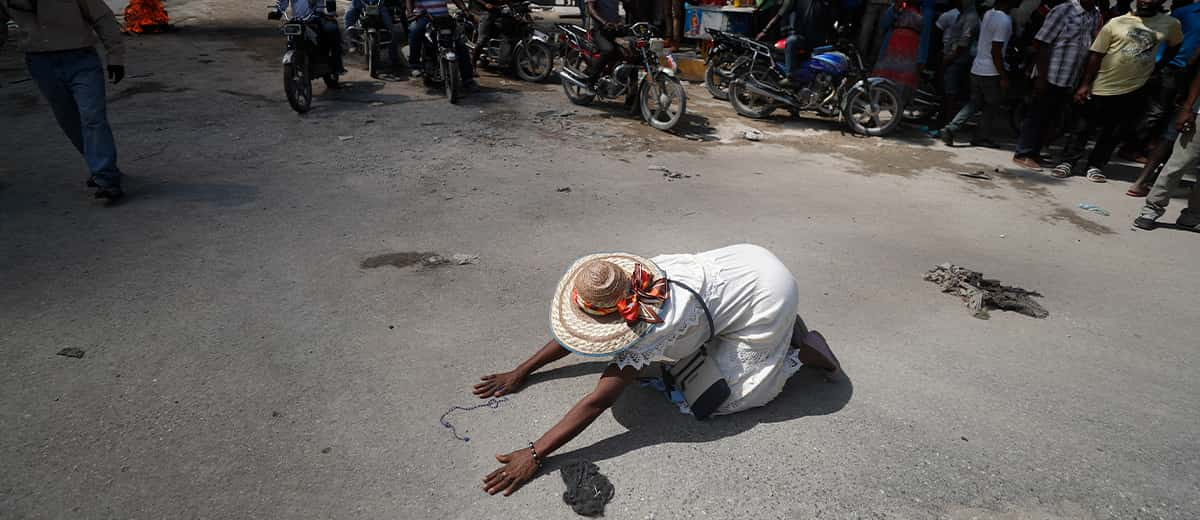 Photo of a woman dropping to the ground during a march in Haiti