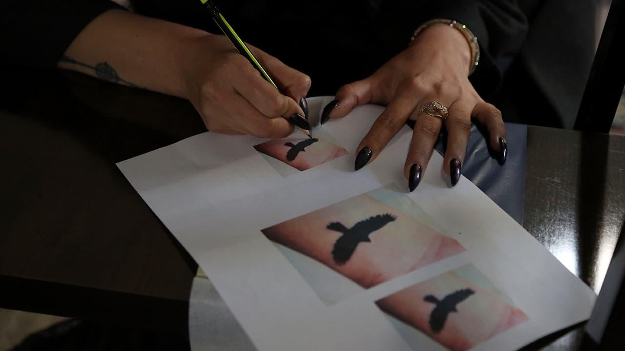 Photo of Suraya Shaheedi, 26, taking a copy of a tattoo