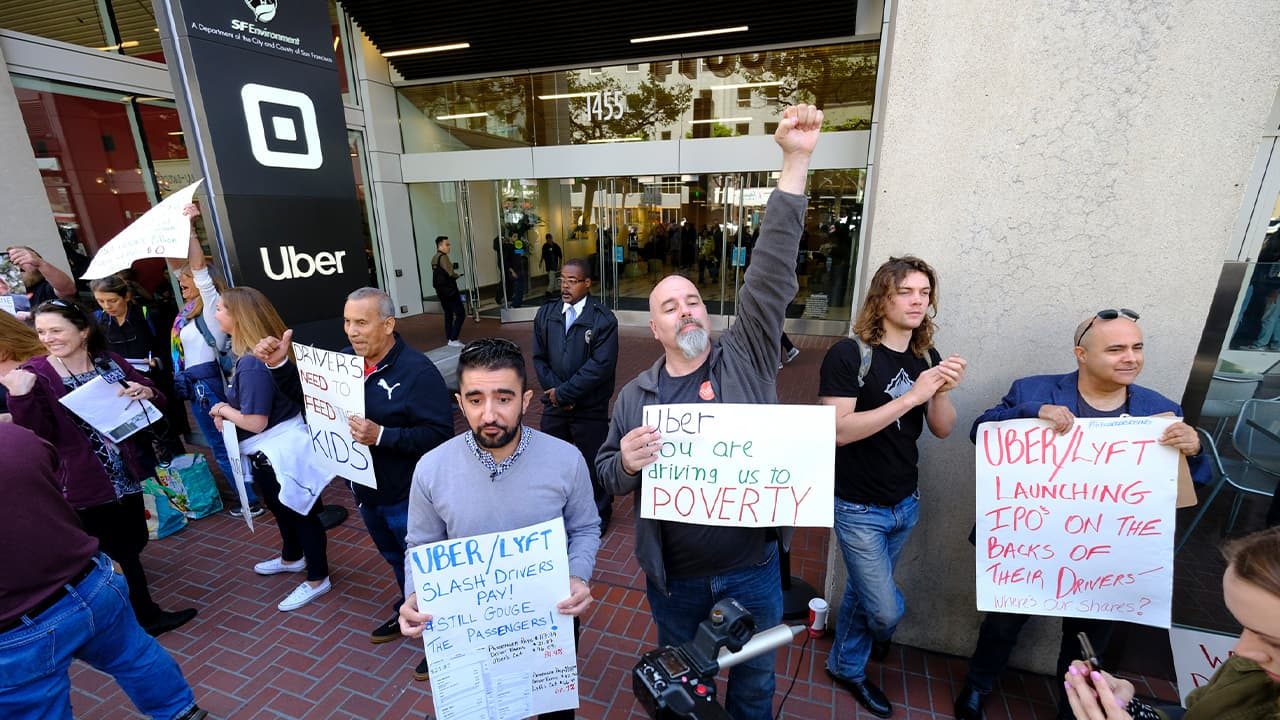 Photo of Uber and Lyft drivers carryh signs during a demonstration
