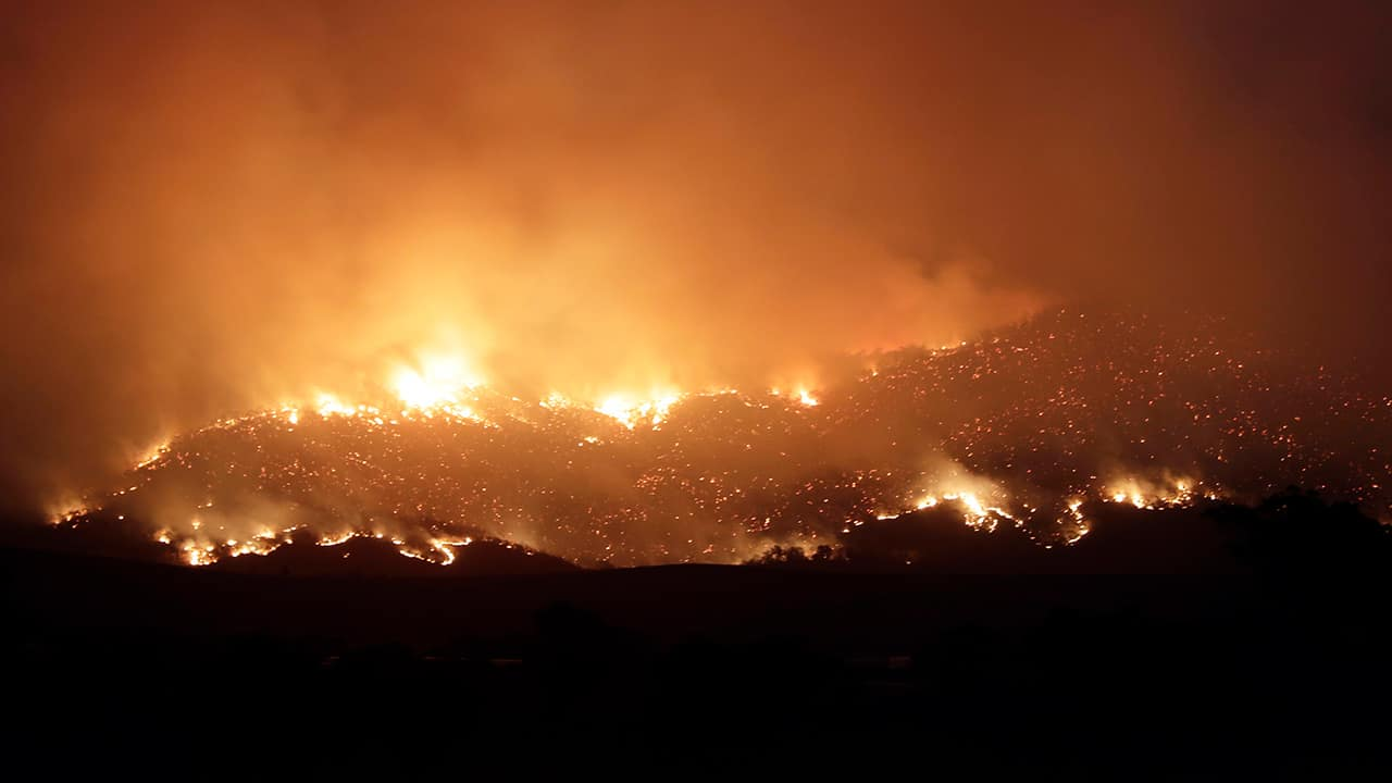Photo of a wildfire threatening property glows on the hills near Clear Range, south of the Australian capital, Canberra