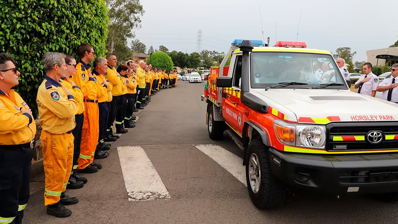 Photo of New South Wales Rural Fire Service crew watch as the casket of NSW RFS volunteer Andrew O'Dwyer arrives for his funeral