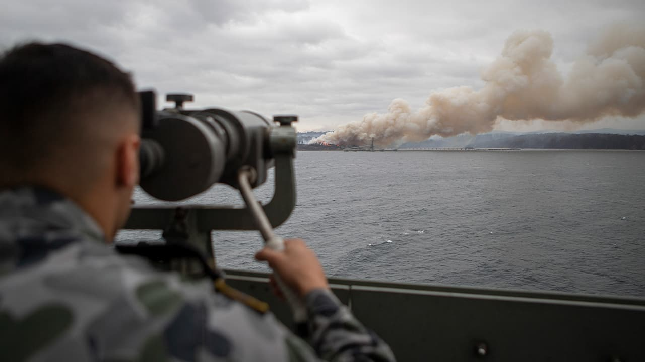 Photo of Seaman Boatswains Mate Malik El-Leissy watches a burning fire from HMAS Adelaide as the ship arrives at Eden to assist with wildfires