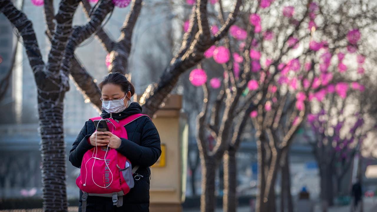 Photo of a woman wearing a face mask as she walks in Beijing